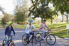Parents and young son cycling together through a park Royalty Free Stock Images