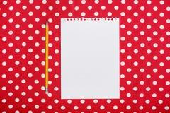 Parer et crayon vides sur la surface rouge et blanche Photographie stock