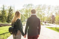 Pares à moda bonitos novos no amor que guarda as mãos na rua, vista traseira Imagens de Stock