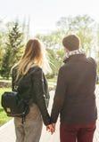 Pares à moda bonitos novos no amor que guarda as mãos na rua, vista traseira Foto de Stock Royalty Free