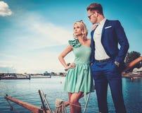 Pares à moda em um iate Fotos de Stock Royalty Free