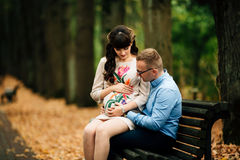 Pares à moda grávidos bonitos que relaxam fora no parque do outono que senta-se no banco Fotos de Stock