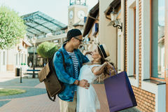 Pares à moda novos com os sacos de compras que abraçam na rua Imagens de Stock