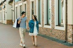 Pares à moda novos com os sacos de compras que guardam as mãos e que andam na cidade Fotografia de Stock Royalty Free