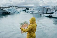Pares à moda novos em Islândia perto da lagoa glacial imagem de stock