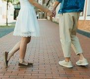 Pares à moda novos que guardam as mãos na rua Imagem de Stock