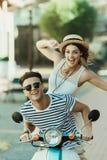Pares à moda novos que têm o divertimento e que montam o 'trotinette' na cidade Imagem de Stock Royalty Free