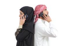 Pares árabes distantes que chamam o telefone foto de stock