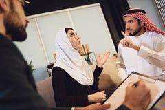 Pares árabes en la recepción con una discusión del terapeuta fotos de archivo