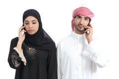 Pares árabes enojados no telefone Fotografia de Stock