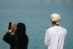 Pares árabes que disfrutan de la vista del puerto en una ciudad grande foto de archivo