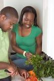 Pares étnicos novos na cozinha que corta vegetais Fotografia de Stock