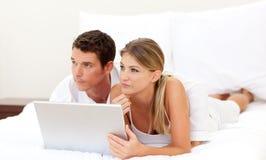 Pares íntimos usando una computadora portátil foto de archivo