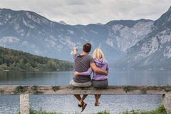 Pares abrazados que miran escena cubierta tranquila de la mañana en el lago Bohinj, montañas de las montañas, Eslovenia imagen de archivo libre de regalías