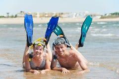 Pares activos en la playa del mar con el conjunto del tubo respirador Imagen de archivo libre de regalías