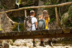 Pares activos que descansan sobre un puente de madera sobre cala de la montaña Imagenes de archivo