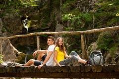 Pares activos que descansan sobre un puente de madera sobre cala de la montaña Fotografía de archivo