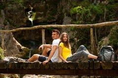 Pares activos que descansan sobre un puente de madera sobre cala de la montaña Foto de archivo