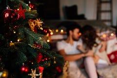 Pares adentro en los pijamas que descansan sobre el piso al lado de la cama cerca del árbol de navidad Foto de archivo