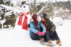 Pares adolescentes al lado del muñeco de nieve con la bebida caliente Fotografía de archivo
