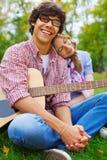 Pares adolescentes alegres con la guitarra en parque Imagen de archivo libre de regalías