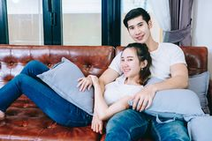 Pares adolescentes asiáticos que olham a tevê junto felizmente Fotos de Stock