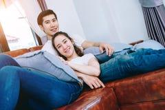 Pares adolescentes asiáticos que olham a tevê junto felizmente Foto de Stock