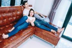 Pares adolescentes asiáticos que olham a tevê junto felizmente Fotografia de Stock