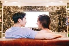 Pares adolescentes asiáticos que ven la TV junto Imagen de archivo libre de regalías