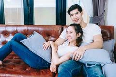 Pares adolescentes asiáticos que ven la TV junto feliz Fotos de archivo