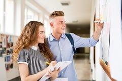 Pares adolescentes atractivos del estudiante en pasillo de la High School secundaria Foto de archivo