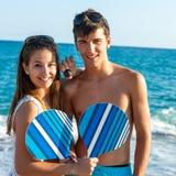 Pares adolescentes com as raquetes de tênis da praia. Fotografia de Stock