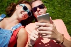 Pares adolescentes con el smartphone que miente en hierba Imagen de archivo libre de regalías