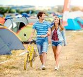 Pares adolescentes con la bici amarilla en el festival de música del verano Foto de archivo