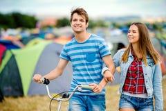 Pares adolescentes con la bici en el festival de música del verano Fotos de archivo