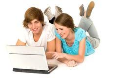 Pares adolescentes con la computadora portátil Imagen de archivo libre de regalías