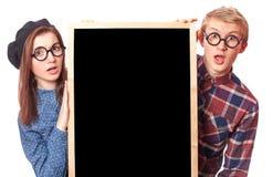 Pares adolescentes con la pizarra. Imagenes de archivo