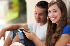 Pares adolescentes con la tablilla digital Fotos de archivo libres de regalías