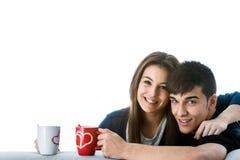 Pares adolescentes con las tazas de café. Foto de archivo