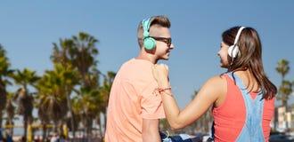 Pares adolescentes con los auriculares en la playa de Venecia Imagen de archivo