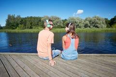 Pares adolescentes con los auriculares en litera del río Fotografía de archivo