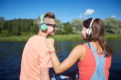 Pares adolescentes con los auriculares en litera del río Imagen de archivo