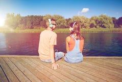 Pares adolescentes con los auriculares en litera del río Imagenes de archivo