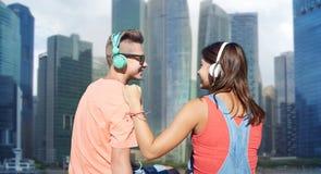 Pares adolescentes con los auriculares en litera del río Foto de archivo