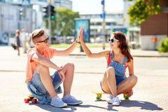Pares adolescentes con los monopatines en la calle de la ciudad Foto de archivo libre de regalías