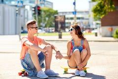 Pares adolescentes con los monopatines en la calle de la ciudad Fotografía de archivo libre de regalías