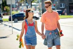 Pares adolescentes con los monopatines en la calle de la ciudad Fotos de archivo