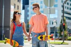 Pares adolescentes con los monopatines en la calle de la ciudad Foto de archivo