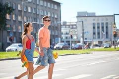 Pares adolescentes con los monopatines en la calle de la ciudad Fotografía de archivo
