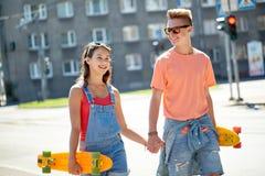 Pares adolescentes con los monopatines en la calle de la ciudad Imágenes de archivo libres de regalías
